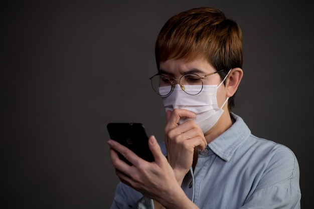 Persona che indossa una maschera chirurgica e usa il telefono con aria preoccupata e preoccupata per l'epidemia di pandemia e notizie dai social media Foto Premium