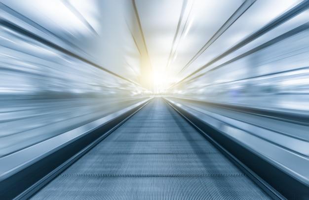 Prospettiva grandangolo in bianco e nero della moderna luce blu illuminata e spaziosa ad alta velocità mobile scala mobile con veloce percorso offuscata di corrimano nel movimento di traffico vanishing Foto Premium