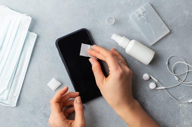 Disinfezione dello schermo del telefono pulire la donna che rimuove i germi con salviette antibatteriche per il virus corona covid-19 Foto Premium