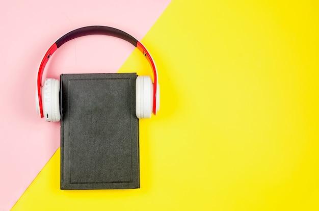 Telefono con auricolari e libro su sfondo di carta colorata. concetto di audiolibro. Foto Premium