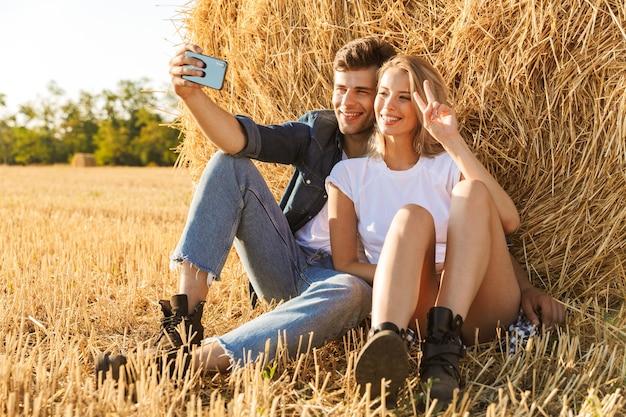 Foto di affascinante coppia uomo e donna che prendono selfie seduti sotto un grande pagliaio in campo dorato, durante la giornata di sole Foto Premium