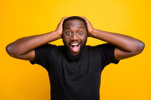 Foto di allegro positivo divertente carino uomo nero felicissimo per il centro commerciale scontato afferrando la sua testa con le mani in t-shirt isolato colore vibrante parete gialla Foto Premium