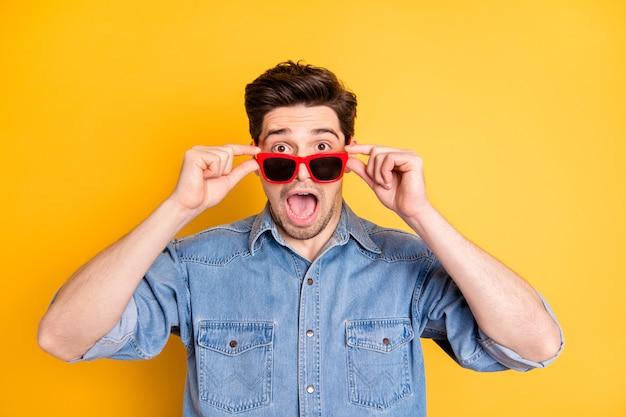 Foto di stupore pazzo uomo che indossa occhiali da sole rossi scioccato per le vendite nella parete di colori vivaci isolata usura degli occhi Foto Premium