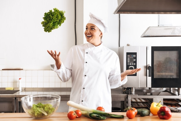 Foto del cuoco unico europeo della donna che indossa un pasto di cottura uniforme bianco con verdure fresche, in cucina al ristorante Foto Premium