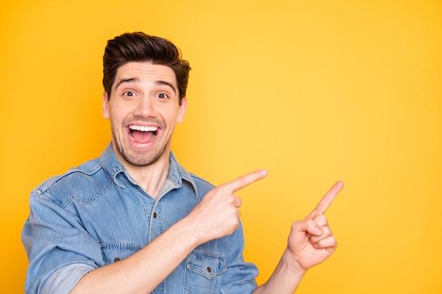 Foto di eccitato estatico uomo felicissimo che grida indicando nello spazio vuoto alle vendite con stupore sul viso isolato vivido muro di colore Foto Premium