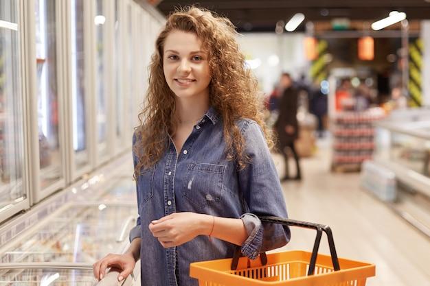 Foto di una donna con i capelli ricci e un aspetto attraente, detiene il carrello, acquista i prodotti in un supermercato, cerca i prodotti necessari nella drogheria. Foto Premium