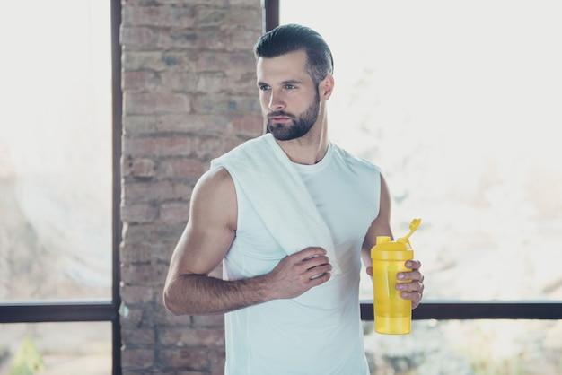 La foto del bel ragazzo sportivo ha terminato l'allenamento mattutino bevendo acqua fresca tenendo l'asciugamano guardando le finestre della casa di addestramento della canotta sportiva laterale concentrata all'interno Foto Premium