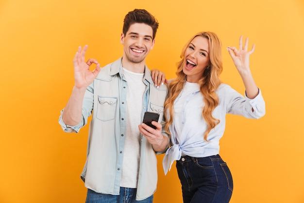 Foto di coppia gioiosa uomo e donna sorridente e mostrando segni ok mentre si tiene smartphone, isolato sopra la parete gialla Foto Premium