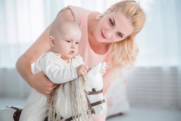 La foto della madre fa rotolare il suo piccolo figlio su un cavallo giocattolo Foto Premium