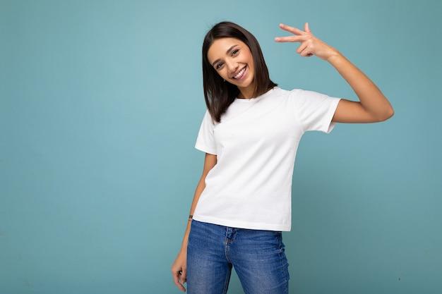 Foto di giovane bella donna castana gioiosa sorridente positiva con emozioni sincere che indossa la maglietta bianca casuale per il modello isolato sopra priorità bassa blu con lo spazio della copia. Foto Premium