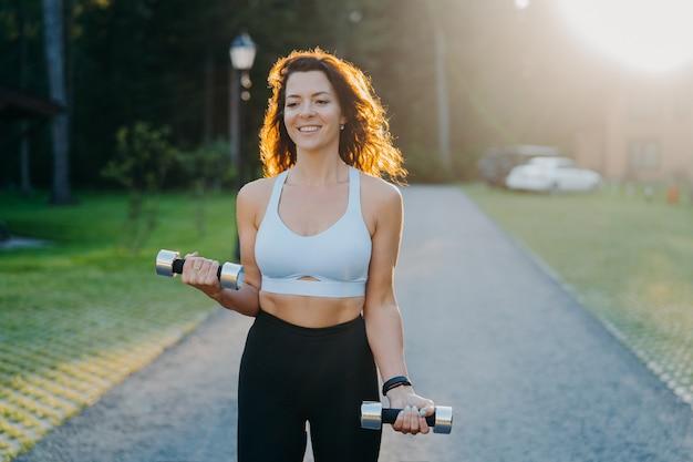 La foto della giovane donna castana esile solleva i manubri ha pose di allenamento mattutine contro l'alba vestita con un top corto e leggings lavora sui muscoli delle braccia sorrisi conduce positivamente uno stile di vita sportivo Foto Premium