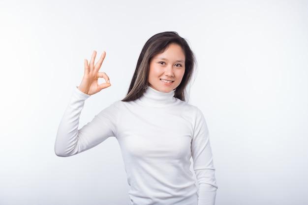 La foto della studentessa sorridente sta mostrando il gesto giusto su fondo bianco. Foto Premium