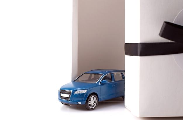 Foto dell'automobile alla moda del suv blu del giocattolo che guida dalla scatola attuale bianca con il grande arco nero isolato sopra fondo bianco. Foto Premium