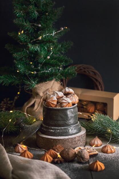 Picci - biscotti di pasta frolla di natale in vaso vintage su sfondo di rami di abete. Foto Premium