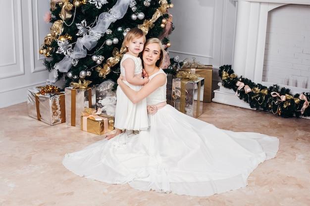 Immagine della famiglia caucasica di madre e figlia a capodanno con doni intorno all'albero di natale Foto Premium