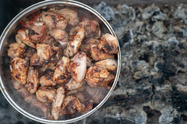 L'immagine di un chiken kebab in una grande padella è in un braciere spento in inverno Foto Premium