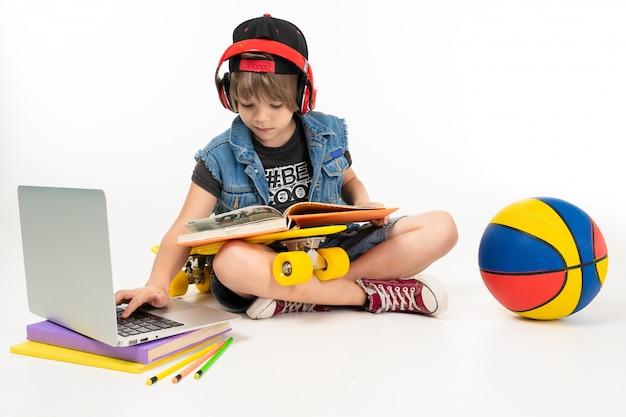 L'immagine di un ragazzo adolescente si siede sul pavimento in giacca di jeans e pantaloncini. scarpe da ginnastica con penny giallo, auricolari rossi, laptop, palla e giocare a giochi per computer o fare i compiti isolati Foto Premium
