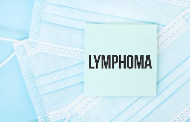 Pezzo di carta con la frase lymphoma sul mucchio di maschere mediche blu Foto Premium