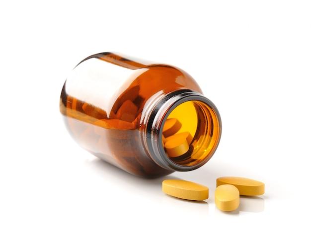 Pillole dalla bottiglia sul bianco Foto Premium