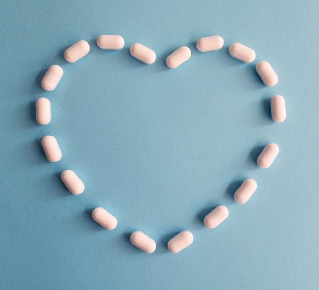 Pillole a forma di cuore su uno sfondo blu Foto Premium