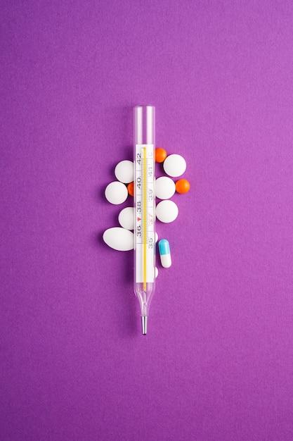 Pillole, compresse e termometro analogico sulla superficie viola viola Foto Premium