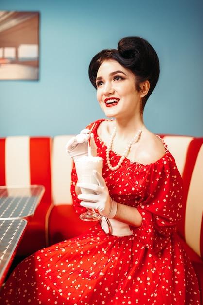 Pin up girl beve milkshake con una cannuccia Foto Premium