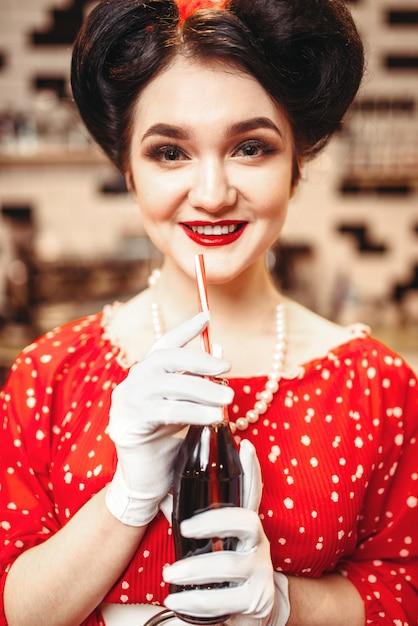 Pin up girl con trucco che beve popolare bevanda gassata, 50 moda americana. abito rosso con pois, stile vintage Foto Premium