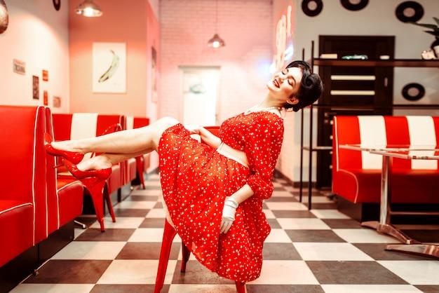 Pin up girl con il trucco in posa sulla sedia in retro cafe, 50 moda americana. scarpe rosse e vestito a pois, stile vintage Foto Premium
