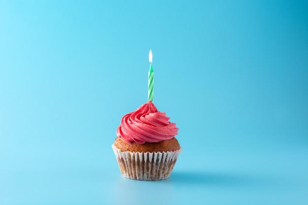 Cupcake compleanno rosa con candela verde su sfondo blu Foto Premium