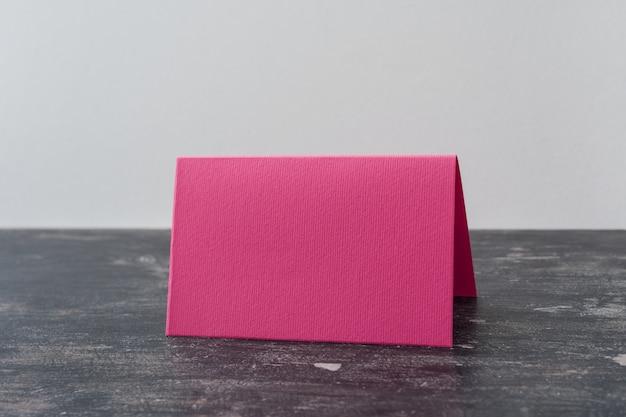 Carta in bianco rosa sul tavolo scuro. Foto Premium