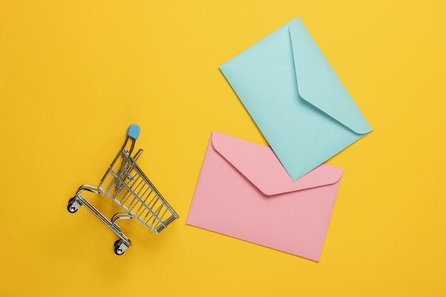 Rosa e blu due buste e carrello della spesa su sfondo giallo. mockup per san valentino, matrimonio o compleanno Foto Premium