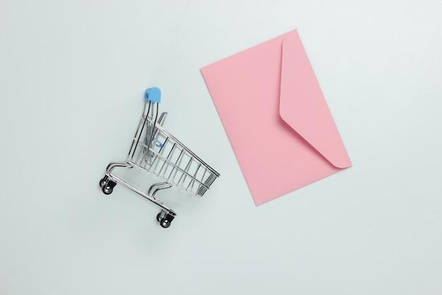 Busta rosa e carrello della spesa su sfondo bianco. mockup per san valentino, matrimonio o compleanno. vista dall'alto Foto Premium