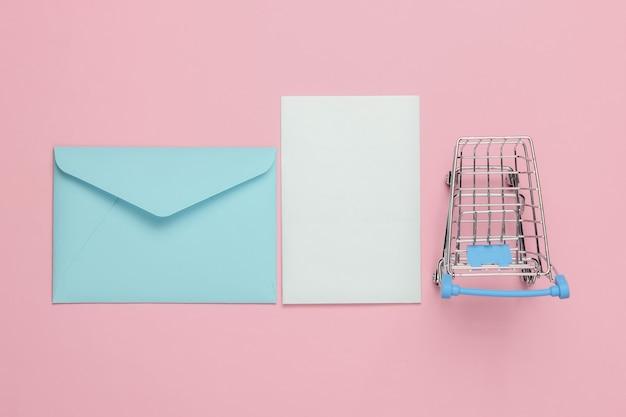 Busta rosa con lettera e carrello della spesa su sfondo rosa pastello. mockup per san valentino, matrimonio o compleanno. vista dall'alto Foto Premium