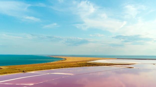 Lago e spiaggia sabbiosa rosa con una baia del mare sotto un cielo blu con le nuvole Foto Premium