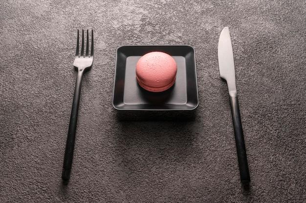 Torta amaretto rosa in un piccolo piatto nero. una bella foto di cibo, un concetto per la progettazione di una caffetteria o un bar, un ristorante. sfondo scuro grunge, tavola. Foto Premium