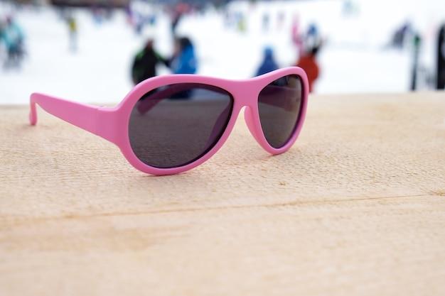 Occhiali da sole cerchiati di rosa sul pendio di legno in apres ski bar o caffetteria, con piste da sci in background, copia dello spazio. concetto di sport invernali, tempo libero, ricreazione, relax Foto Premium