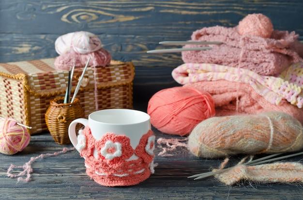 Filato rosa e oggetti artigianali su un tavolo di legno Foto Premium