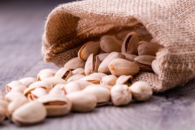 Noce di pistacchi nel sacco di tela ruvida su fondo di legno granuloso. Foto Premium