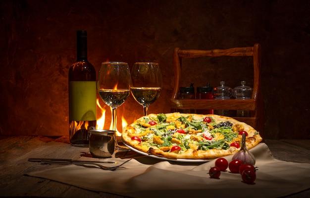 Pizza, bottiglia di vino bianco e due bicchieri di vino contro il camino. atmosfera romantica serale nel ristorante italiano. Foto Premium