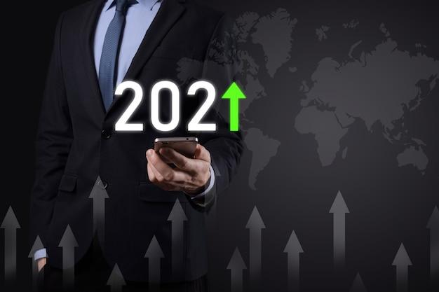 Pianificare la crescita positiva del business nel concetto di anno 2021. piano dell'uomo d'affari e aumento degli indicatori positivi nella sua attività, crescendo concetti di business. Foto Premium