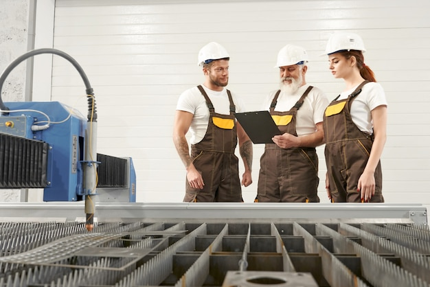 Plasma cutter e tre ingegneri che parlano, guardando la cartella Foto Premium