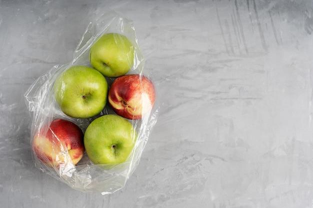 Sacchetto di plastica pieno di mele mature e nettarine su cemento Foto Premium