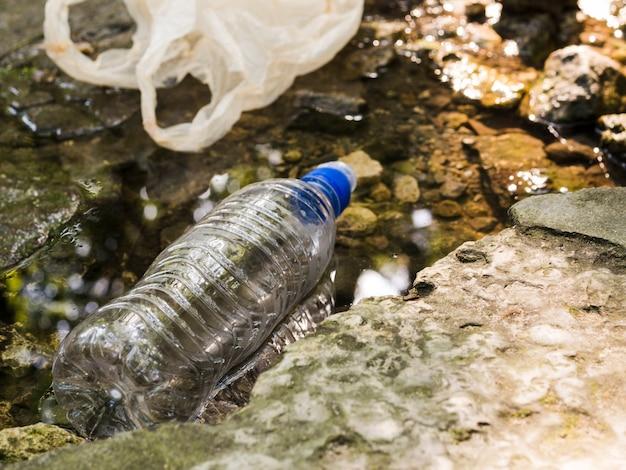 Bottiglia e borsa di plastica che galleggiano in acqua all'aperto Foto Premium