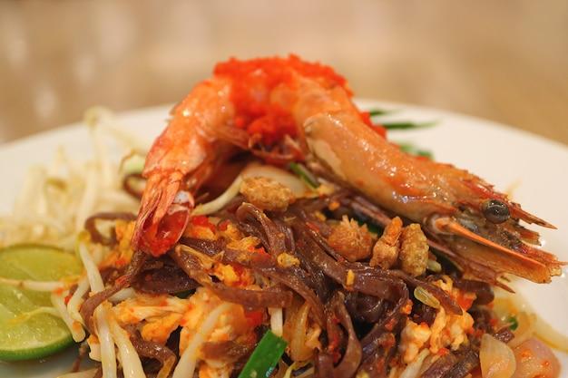 Piatto di pad thai o thai style noodle saltati in padella condita con gamberetti interi Foto Premium
