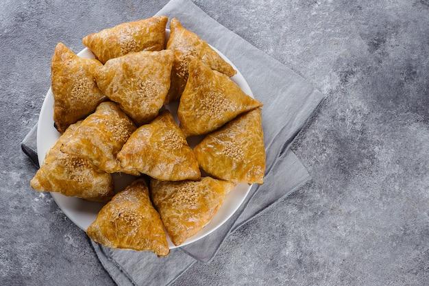 Piatto con il samsas delizioso di samosa con carne su fondo grigio, vista superiore. cibo uzbeko Foto Premium