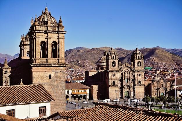 Plaza de armas, cattedrale e chiesa della compagnia di gesù o iglesia de la compania de jesus. cusco, perù. cielo blu in una bella giornata estiva. Foto Premium