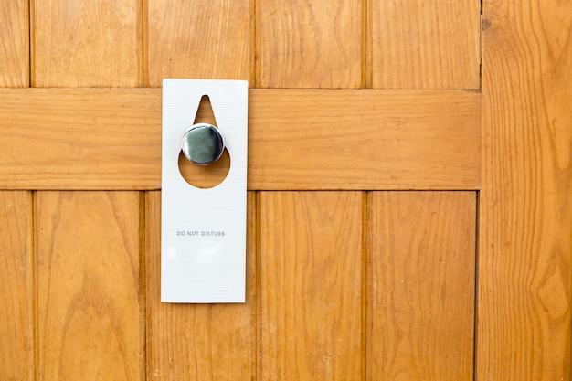 Si prega di non disturbare il segno sulla porta in legno chiusa della camera d'albergo Foto Premium