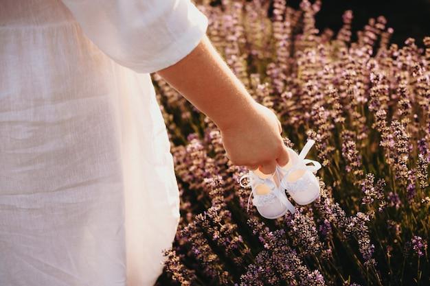 Madre grassoccia con in mano un paio di scarpette e cammina in un campo di lavanda mentre indossa un bel vestito bianco Foto Premium