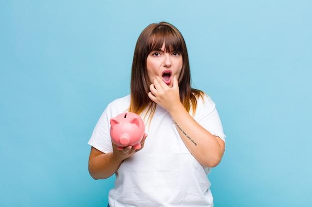 Donna taglie forti con la bocca e gli occhi spalancati e la mano sul mento, che si sente spiacevolmente scioccata, dice cosa o wow Foto Premium