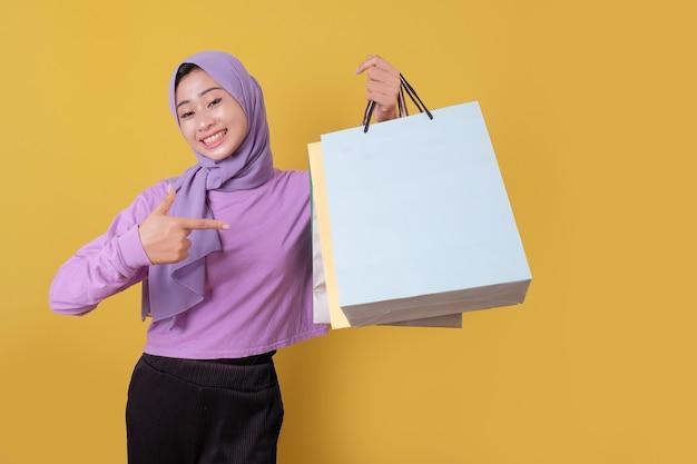 Indicare di bella donna asiatica che mostra le borse della spesa, indossando la maglietta viola Foto Premium